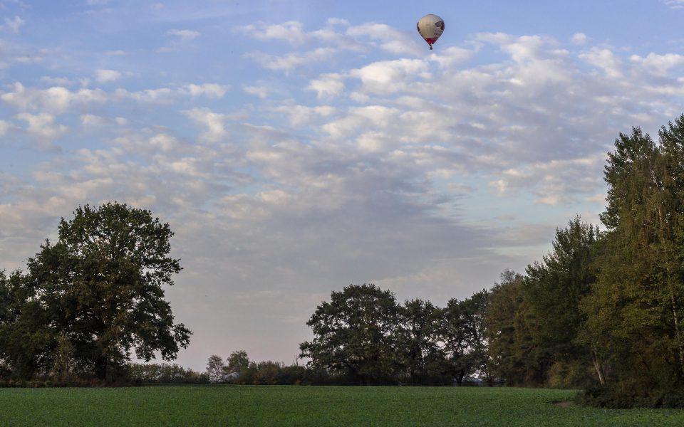 Hintergrundbild - Heißluftballon über Landschaft